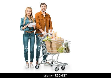Happy girl prüfen Einkaufsliste auf digitalen tablet, während ihr Freund in der Nähe von mit Trolley voller Säcke aus Papier mit Produkten isoliert auf weißem - Stockfoto