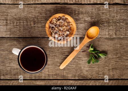 Tasse Tee mit Minze Blatt und braunen Zucker in die Schüssel auf rustikalen Holzmöbeln Hintergrund. Kopieren Sie Platz. Ansicht von oben - Stockfoto