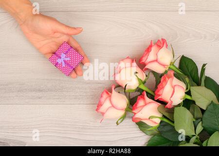 Woman's Hände halten ein Geschenk Box über graues Holz- Hintergrund mit wunderschönen Rosen. Konzept der ein Geschenk an Feiertagen. Ansicht von oben. - Stockfoto