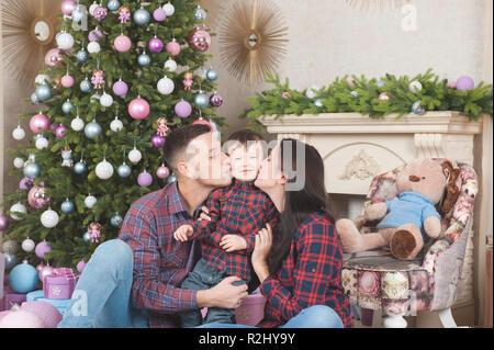 Junge Familie Mann und Frau küssen kleine Zicklein in frohe Weihnachten Dekoration - Stockfoto