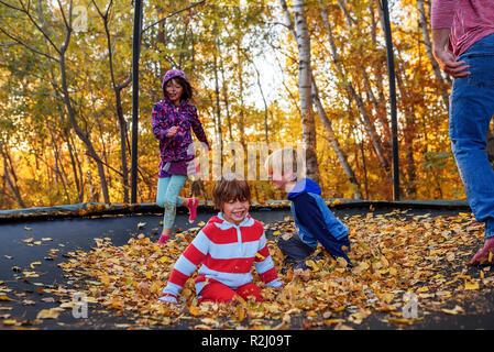 Drei Kinder und ihr Vater, und sie spielen auf einem Trampolin im Herbst die Blätter fallen, United States - Stockfoto