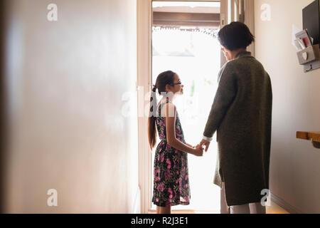Liebevolle Mutter und Tochter halten sich an den Händen in der Tür - Stockfoto