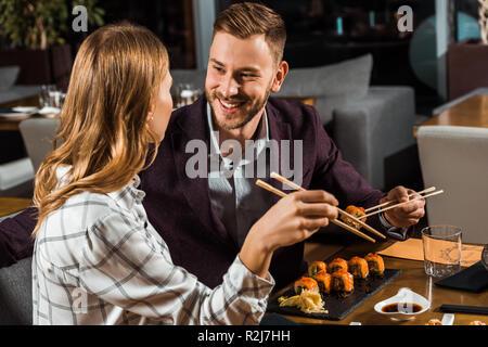 Schöne glückliche Paar essen Sushi Rollen im Restaurant - Stockfoto