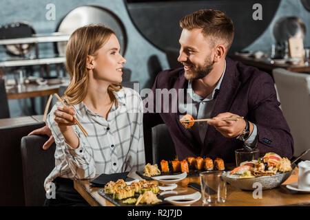 Glückliche junge erwachsene Paare sich einander beim Essen im Restaurant Sushi Rollen - Stockfoto