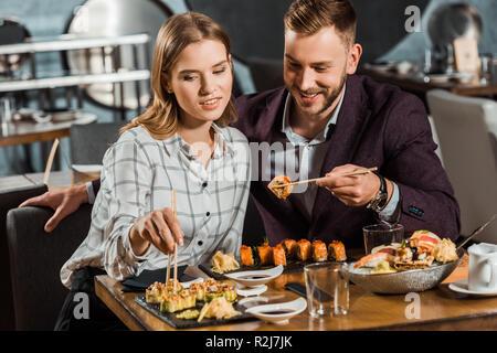Glücklich lächelnde junge erwachsene Paare essen Sushi Rollen im Restaurant - Stockfoto