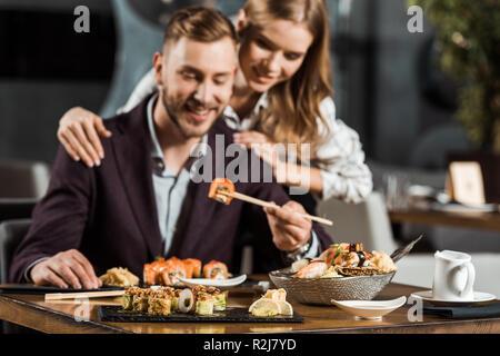 Gerne attraktive Paar Abendessen und das Essen lecker Sushi Rollen im Restaurant - Stockfoto