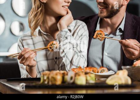 7/8-Ansicht von lächelnden glückliches Paar Sushi essen im Restaurant - Stockfoto