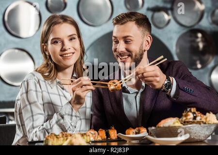 Glückliche junge Erwachsene paar Sushi essen im Restaurant - Stockfoto