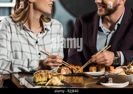 Teilweise mit Blick auf die lächelnde Paar Sushi essen im Restaurant - Stockfoto