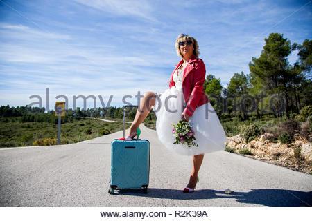 Eine Frau, gekleidet wie eine Braut, die, mit einer roten Jacke, einen Blumenstrauß und ein Bein ruht auf einem Koffer, stellt in der Mitte eines einsamen Weg. - Stockfoto