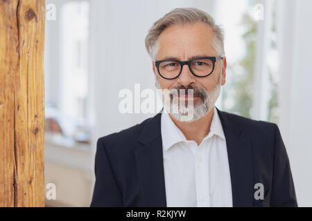 Portrait von eleganten Reife bärtige Mann mit Brille tragen weiße Hemd und Jacke - Stockfoto