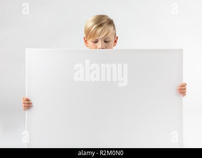 Kleine blonde Junge hält ein Schild in der Hand und sieht nach unten