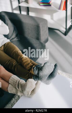 7/8 Schuß von Paar in Wollsocken entspannen auf der Couch zu Hause - Stockfoto