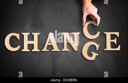Hand bewegt sich eine hölzerne schreiben, drehen das Wort 'Ändern' zu 'Chance' auf einer Tafel - Stockfoto