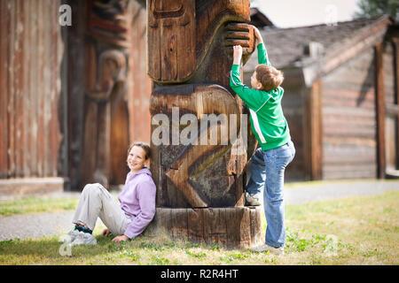 Zwei Kinder neben einem Totempfahl. - Stockfoto
