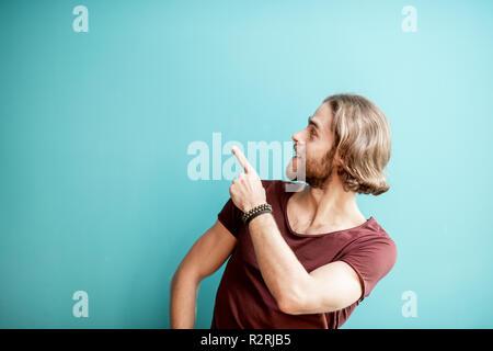 Portrait einer jungen kaukasischen bärtiger Mann mit langem Haar gekleidet in t-shirt, mit der Hand auf dem bunten Hintergrund - Stockfoto