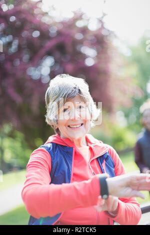 Porträt Lächeln, zuversichtlich Active Senior Frau Kontrolle smart Watch in Park - Stockfoto