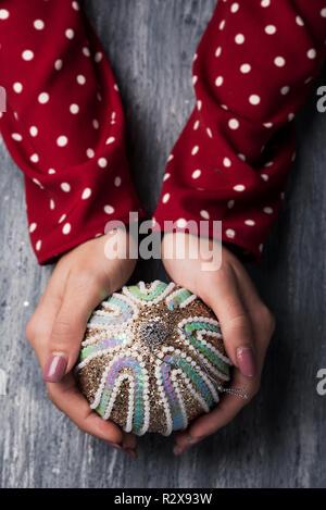 Hohe Betrachtungswinkel von einer weißen Frau mit einem verzierten Christmas Ball in den Händen auf einem grauen rustikalen Holztisch - Stockfoto
