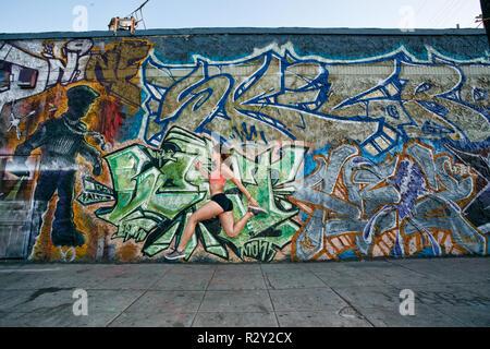 Weibliche Athleten entlang der Bürgersteig letzten Gebäude in Graffiti bedeckt. - Stockfoto