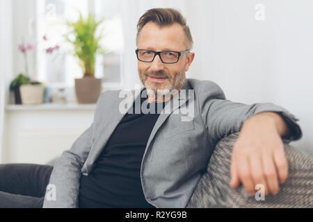 Portrait von bärtigen reifer Mann tragen graue Jacke sitzt auf einem Sofa - Stockfoto