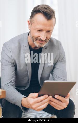 Portrait von reifer Mann tragen graue Jacke mit digitalen Tablet - Stockfoto
