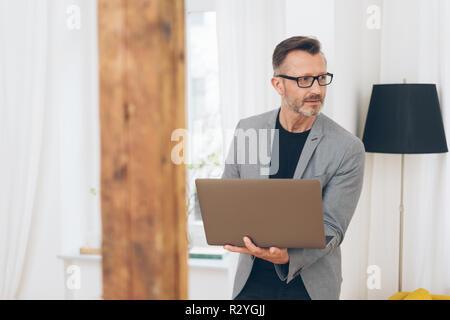 Portrait von reifer Mann tragen graue Jacke und Gläser mit Laptop zu Hause stehend - Stockfoto