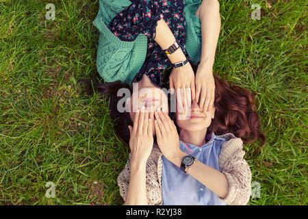 Blick von oben auf die lächelnde Freunde liegen auf Gras Spaß haben, schliessen die Augen mit den Händen. Schwestern Zeit miteinander zu verbringen. - Stockfoto