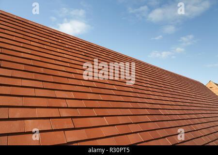Neue traditionelle Flachziegel auf einem Hausdach gegen einen blauen Himmel mit Kopie Raum - Stockfoto