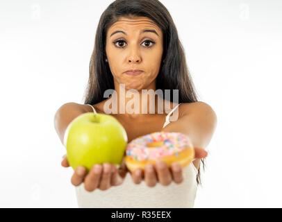 Schöne junge Frau versucht, die Wahl zwischen Apple und Krapfen in Gesund ungesunde Nahrung, Detox essen, Kalorien und Diät Konzept zu machen. - Stockfoto