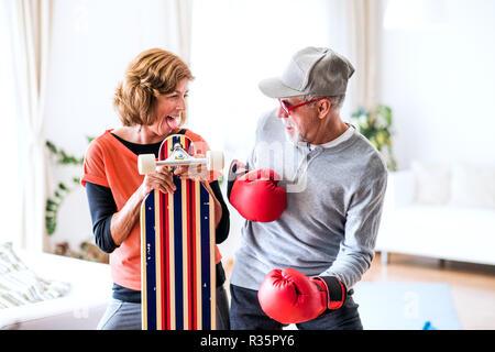 Senior Paar mit Boxhandschuhen und longboard Spaß zu Hause haben. - Stockfoto