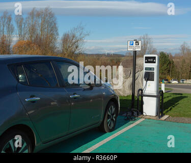 Auto Elektrofahrzeug aufladen Punkt mit Windkraftanlagen im Hintergrund - Stockfoto