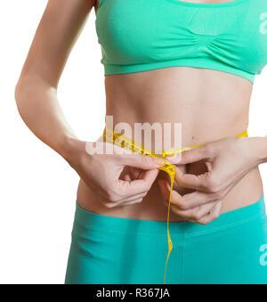 Fit und Gesund junge Frau messen ihre Taille mit einem Maßband isoliert auf Weiss. - Stockfoto