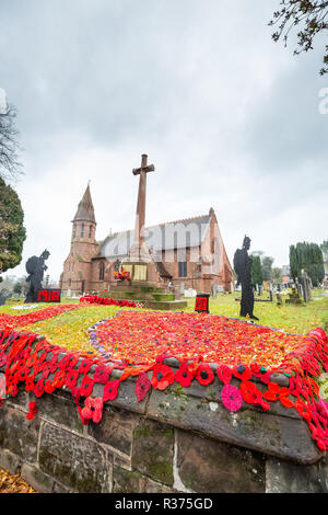 Aus Gewirken und Gestricken roter Mohn auf der Anzeige, zusammen mit der ständigen Soldat Silhouetten, ausserhalb in Großbritannien Kirchhof, War Memorial. Waffenstillstand 100-jähriges Bestehen. - Stockfoto