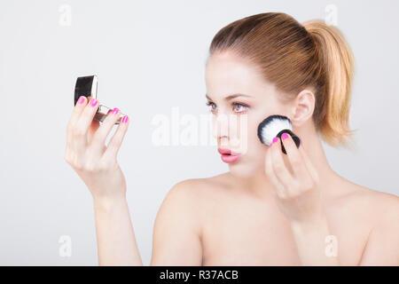 Porträt einer jungen Frau mit einem Kabuki auf ihrem Gesicht und betrachtete sich im Spiegel - Stockfoto