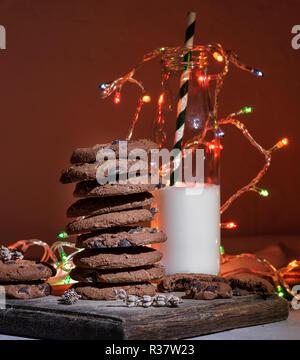 Stapel von Schokolade, Kekse, eine Glasflasche mit Milch und einem hellen Weihnachtsgirlande, festlichen Hintergrund - Stockfoto