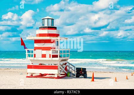 South Beach, Miami, Florida, Rettungsschwimmer Haus in eine bunte Art Deco rot und whhite Stil an bewölkten Himmel und den Atlantik im Hintergrund, weltberühmten Reisen Lage - Stockfoto