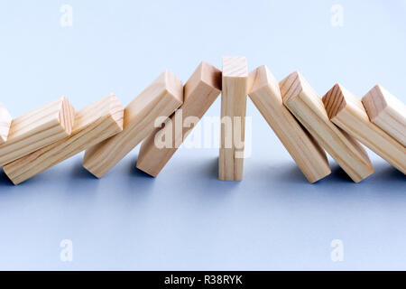Stärke und Führung Business Konzept - ein Holz Spielzeug Block Stop Dominoeffekt - Stockfoto