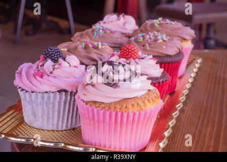 Frisch gebackene leckere verschiedene Cupcakes serviert zusammen mit Holz Hintergrund - Stockfoto