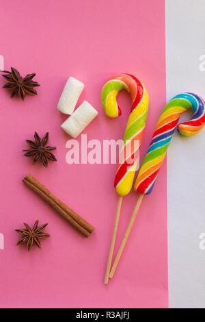 Lutscher auf einem sanften Hintergrund. Weihnachten Candy und Karamell klebt auf Rosa und Gelb Hintergründe - Stockfoto