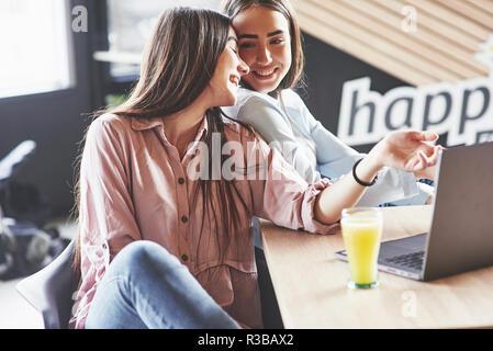 Zwei schöne twin Mädchen verbringen Zeit Saft trinken. Schwestern in ein Cafe und gemeinsam Spaß haben - Stockfoto