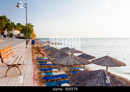 Holzbank, auf Fliesen- Gehweg hinter, aber über dem öffentlichen Strand mit strohgedeckten Sonnenschirmen, Sonnenschirmen und Liegen neben der Küste. - Stockfoto
