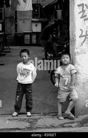 Zwei neugierige Jungen in ''Ihre'' Straße in Shanghai, China. - Stockfoto