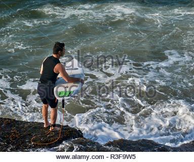 Ein Mann in einem Neoprenanzug mit seinem Surfbrett - Timing sein Eintritt in das Wasser aus einer felsigen Landzunge - Surfen in Turners Beach, Yamba, NSW, Australien. - Stockfoto