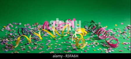 Karneval oder Geburtstagsparty. Konfetti und Serpentinen auf hellen grünen Hintergrund, Banner - Stockfoto