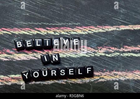 Glauben Sie an sich selbst auf Holzblöcken. Kreuz verarbeitete Bild mit blackboard Hintergrund. Inspiration, Bildung und Motivation Konzepte mit den Worten - Stockfoto