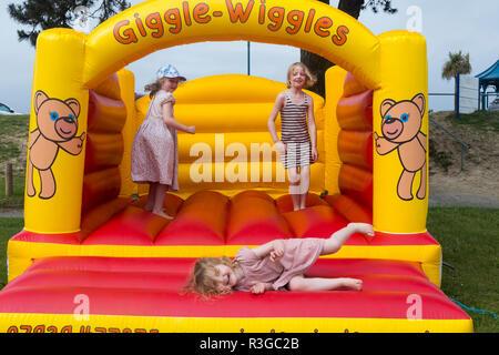 Drei Kinder im Alter von vier, sechs, acht Jahre alt, Spielen/sicher das Aufprallen auf eine aufblasbare Hüpfburg in einem Café/Pub/Restaurant Garten. (98) - Stockfoto