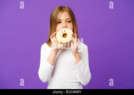 Mädchen, dass große Krapfen mit Puderzucker. Süßes, verglaste Bagel mit Augen. Kind essen lustig Dessert, süße Kindheit. Kind mit langem Haar zu tragen whi - Stockfoto