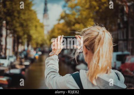 Frau Tourist, der ein Bild von Canal in Amsterdam auf dem Mobiltelefon. Warme gold Nachmittag Sonne. Reisen in Europa. - Stockfoto