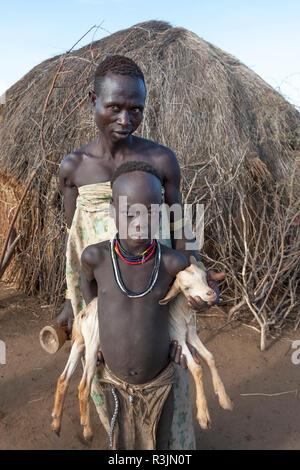 Afrika, Äthiopien, südlichen Omo Valley, Nyangatom Stamm. Porträt einer Nyangton Mann hinter seiner Tochter, die eine junge Ziege stehend. - Stockfoto