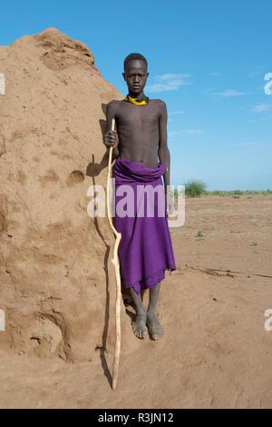 Afrika, Äthiopien, südlichen Omo Valley, Nyangatom Stamm. Portrait einer jungen Nyangatom Junge stand neben einem termitenhügel Damm. - Stockfoto
